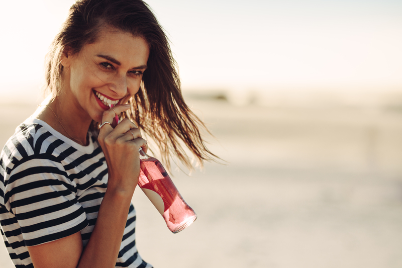 Smiling woman drinking a soft drink